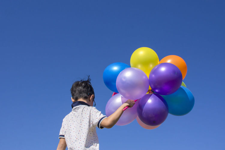 Low angle rear view of boy holding multi colored balloons against clear blue sky