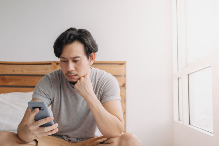 Young man using mobile phone while sitting at home