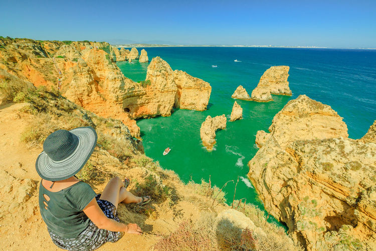 Summer holidays in Algarve, Portugal. Lifestyle tourist with hat sitting on promontory of Ponta da Piedade and overlooks the coast of Lagos with iconic cliffs and limestone. Turquoise sea, sunny day. Portugal Algarve Blue Sky Europe Promontory Ponta Da Piedade Ponta Da Piedade Lagos Lagos Beachphotography Limestone Beach Sea Overlooks San Francisco Bay Aerial View Ocean Woman Girl Females Water Hat Beauty In Nature Scenics - Nature Real People Leisure Activity Rock - Object Land Rear View One Person Day Rock Solid Lifestyles Nature Clothing Outdoors Looking At View
