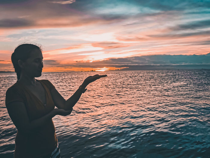 Girl standing by sea against sky during sunset