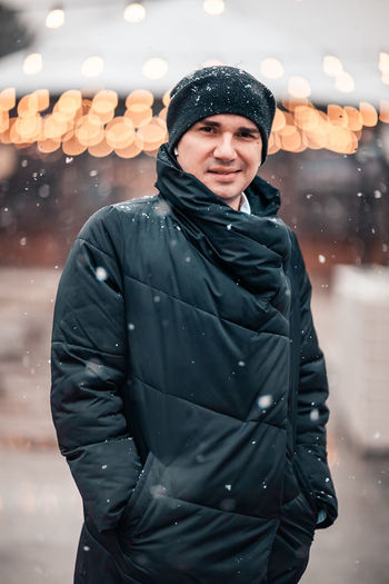 Portrait of man wearing winter coat standing in snow at city street