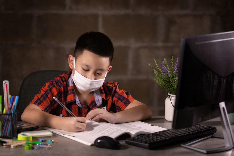 Boy writing on table