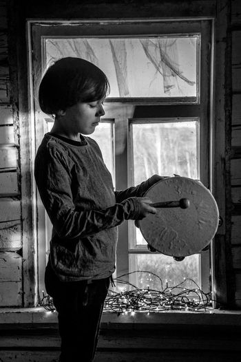 Side view of boy holding window at home
