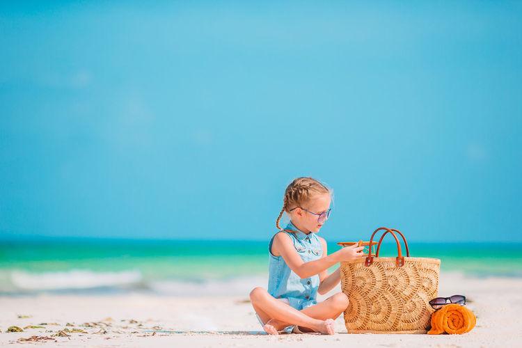 Full length of girl sitting at beach against sky