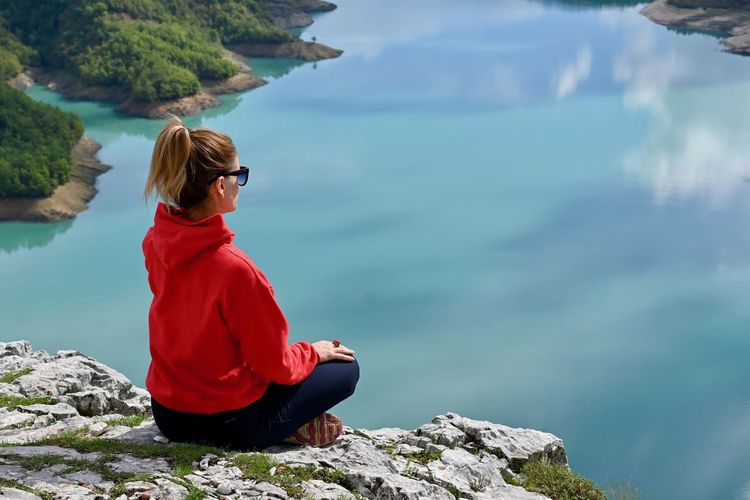 Woman sitting on rock looking at lake
