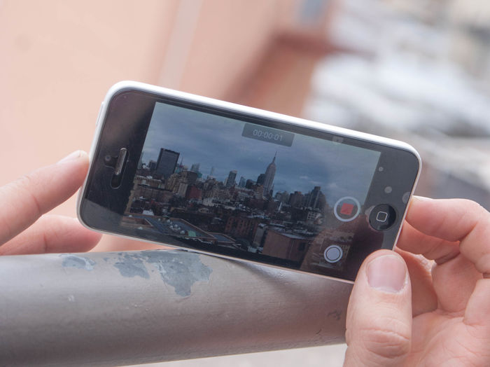 Cropped image of hand photographing cityscape through smart phone