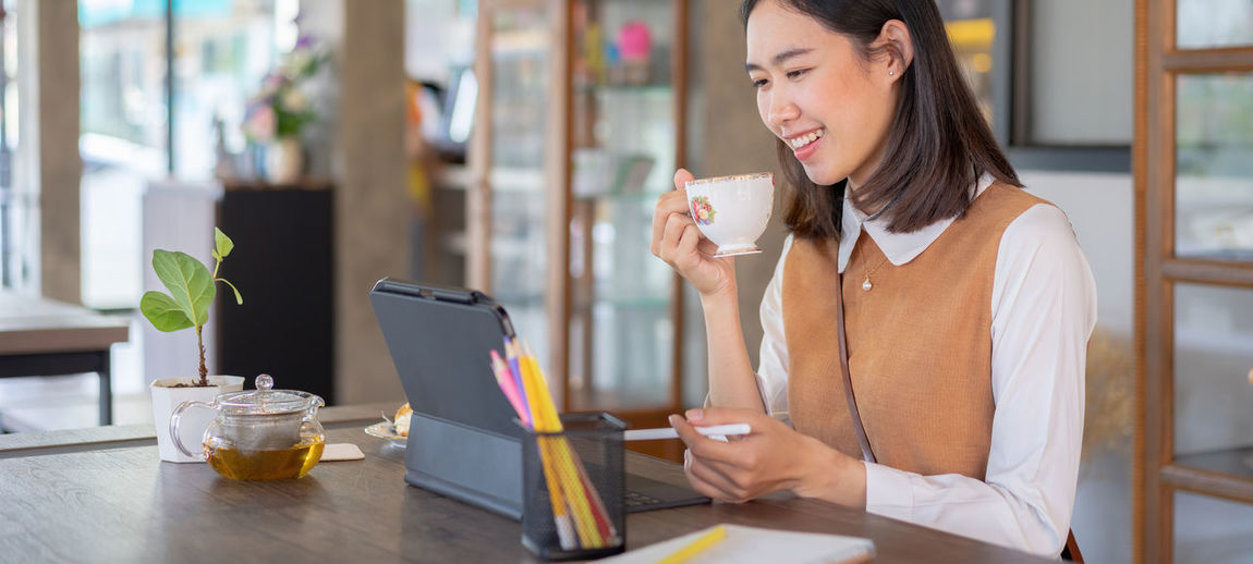Midsection of woman holding smart phone on table