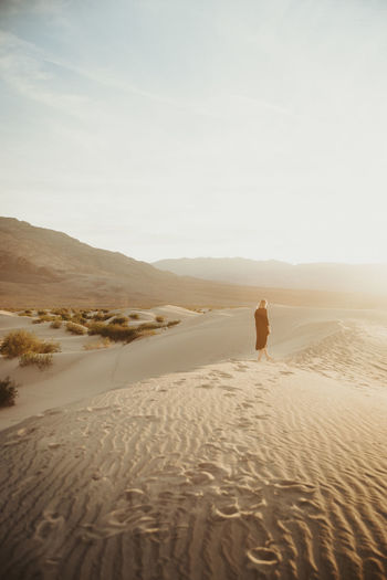 Rear View Of Woman Walking At Desert Against Sky During Sunset