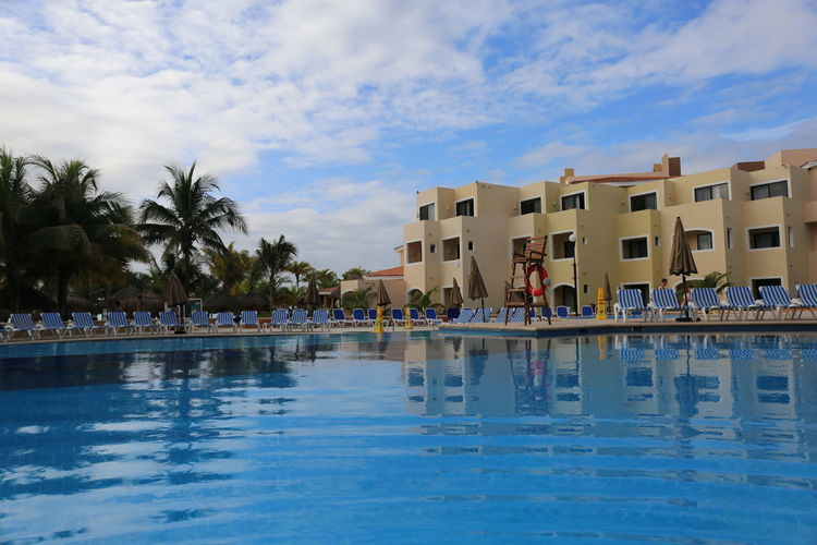 Swimming Pool of the Viva Wyndham Maya Resort in Playa del Carmen Playacar, Mexico Architecture Blue Building Exterior Built Structure Day Hotel Hotel Pool Men Outdoors Palm Tree People Real People Resort Resort Hotel Sky Swimming Pool Tree Vacations Viva Wyndham Maya Water