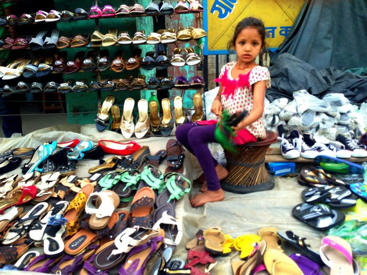 Girl helping her mother by taking care of her mother's shoe shop after her school in an open-air market also called haat bazaar in Nepali at Butwal, Nepal Butwal City Girl Haat Bazaar Iphonography Learn & Shoot: Working To A Brief Open-air Market Outdoors Vendor