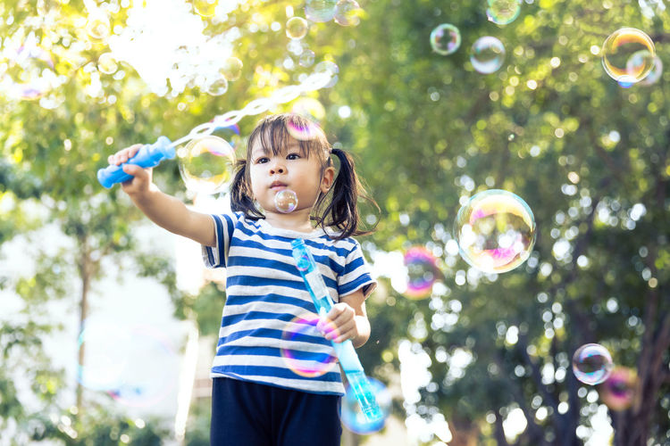 Full length of a girl blowing bubbles