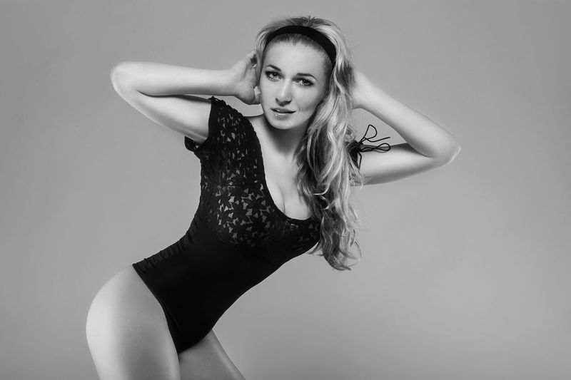 Portrait of beautiful model standing in bodysuit against gray background