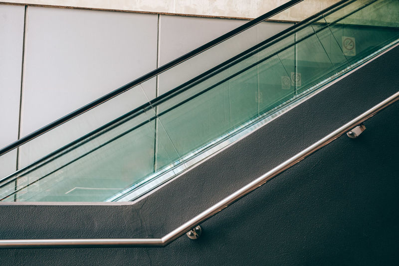 Fragment of escalator and handrail - geometric architectural detail City Life Architectural Detail Architecture Building Built Structure Close-up Convenience Day Escalator Full Frame Glass - Material Indoors  Low Angle View Metal Modern No People Railing Reflection Transparent Transportation Window