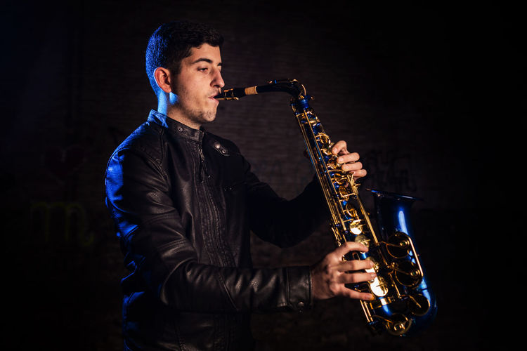 Side View Of Young Man Playing Saxophone Against Black Background