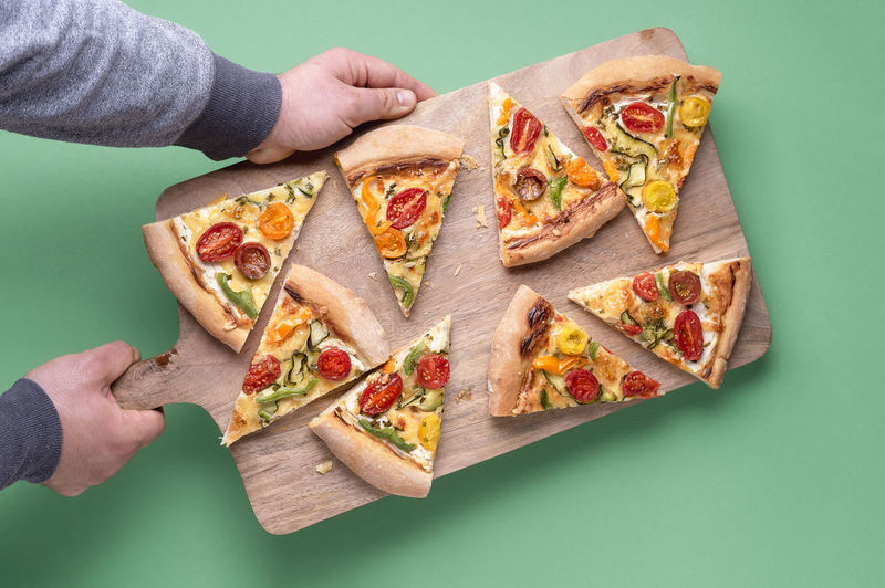 High angle view of hand holding pizza over table against gray background