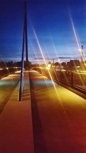 Illuminated road against blue sky at sunset