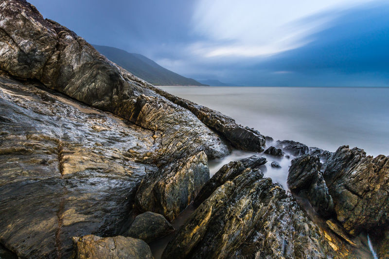 Scenic view of sea by rock formations against cloudy sky