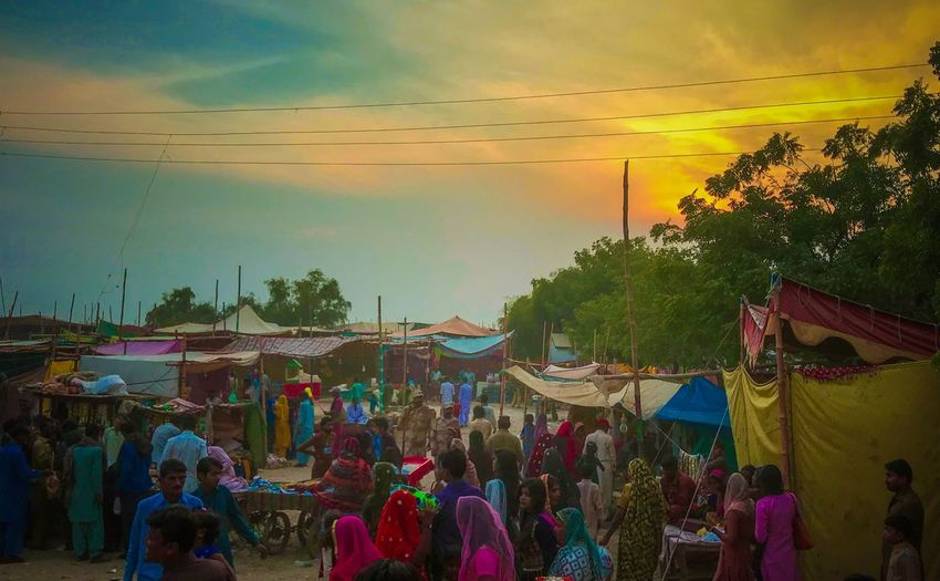 People at market against sky during sunset