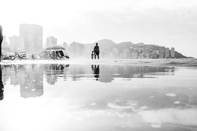 Benidorm Reflections Reflection Building Exterior Water Architecture Built Structure Outdoors Real People Day City One Person Sky Benidorm Nature Men Skyscraper Women Lifestyles Full Length Modern Vacations Beauty In Nature The Great Outdoors - 2018 EyeEm Awards The Street Photographer - 2018 EyeEm Awards