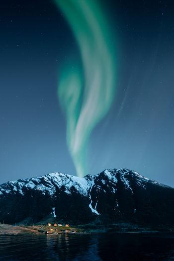 Aurora borealis and mountain landscape with small norwegian village