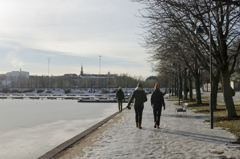 Rear View Of People Walking On Snow Covered Road By River