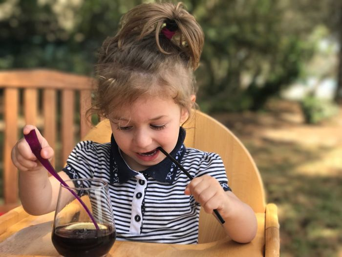 Baby girl with soda holding straw while sitting on chair