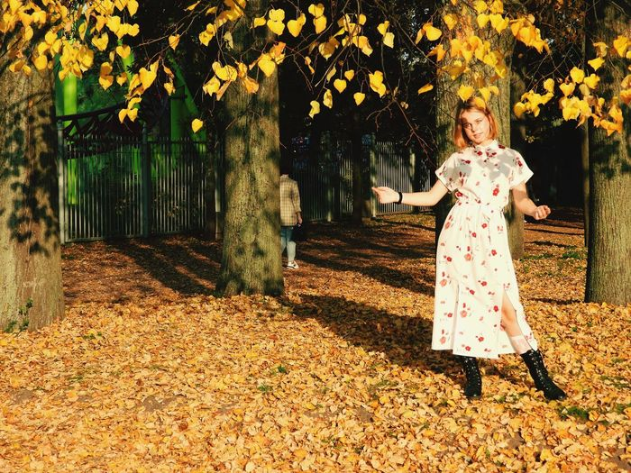 Portrait of woman standing by leaves during autumn