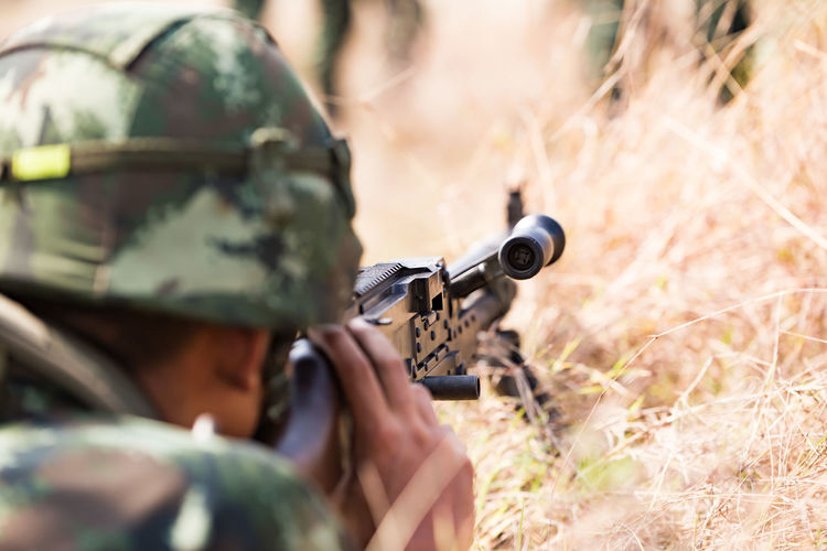 Close-up of army shooting with rifle