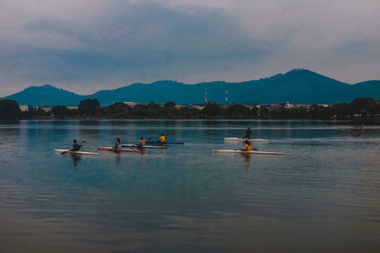 People Rowing In Lake Against Sky