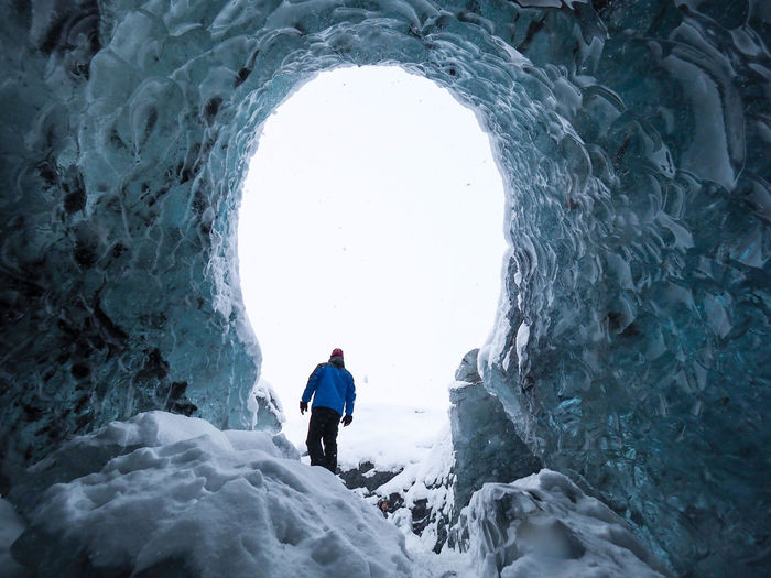 Rear view of man walking on snowcapped mountain