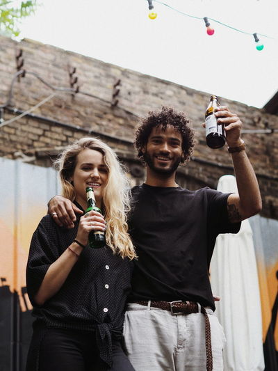 Low angle portrait of smiling friends holding alcoholic drink bottles