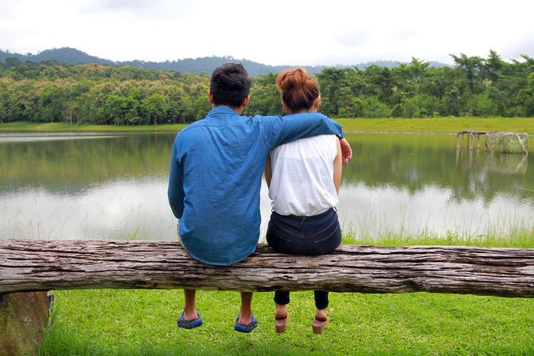 Rear view of couple sitting on lake against trees