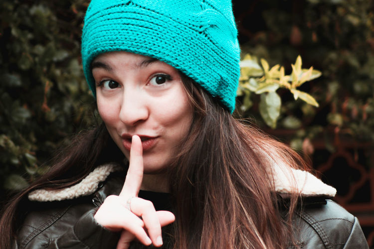 Close-up portrait of young woman with finger on lips against plants during winter