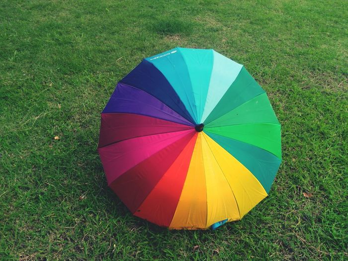 High angle view of multi colored umbrella on field
