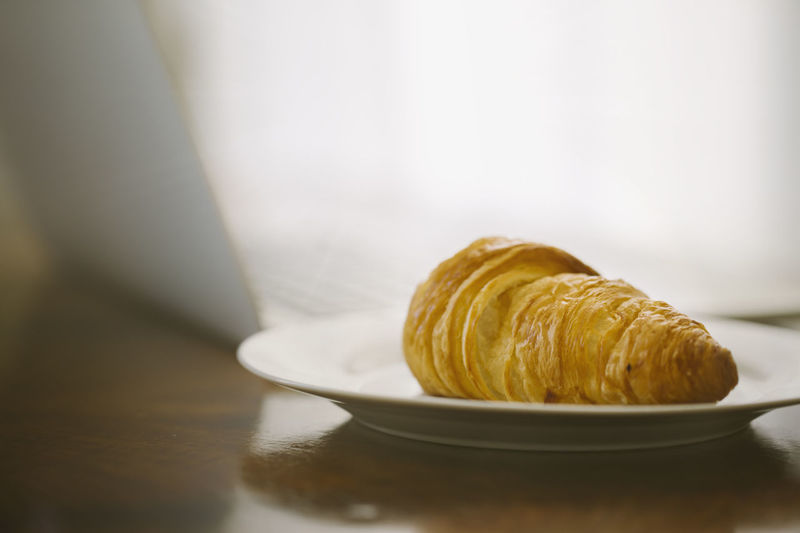 Fresh baked croissants and a laptop with a coffee, morning croissant and work Close-up Croissant Day Food Food And Drink French Food Freshness Indoors  No People Plate Ready-to-eat Sweet Food Table