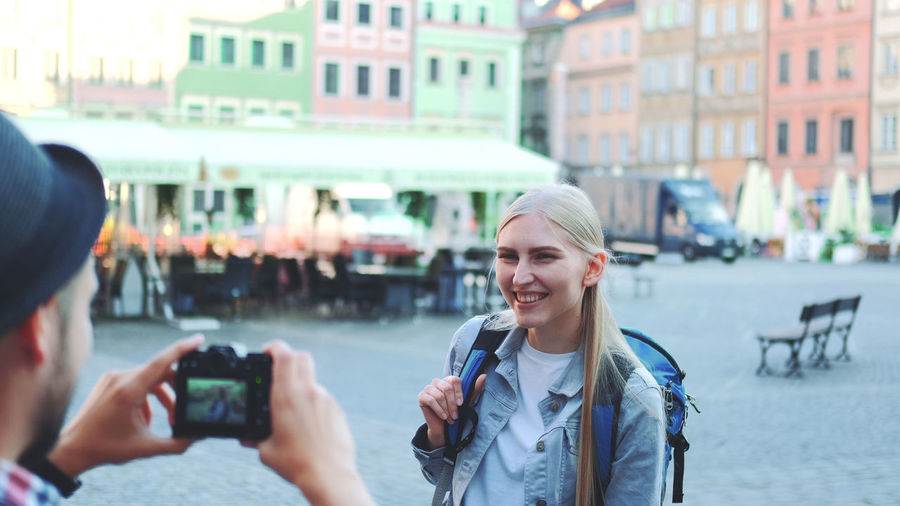 Portrait of woman photographing in city