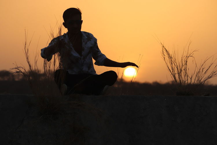 Optical illusion of man protecting sun while sitting on field against sky during sunset