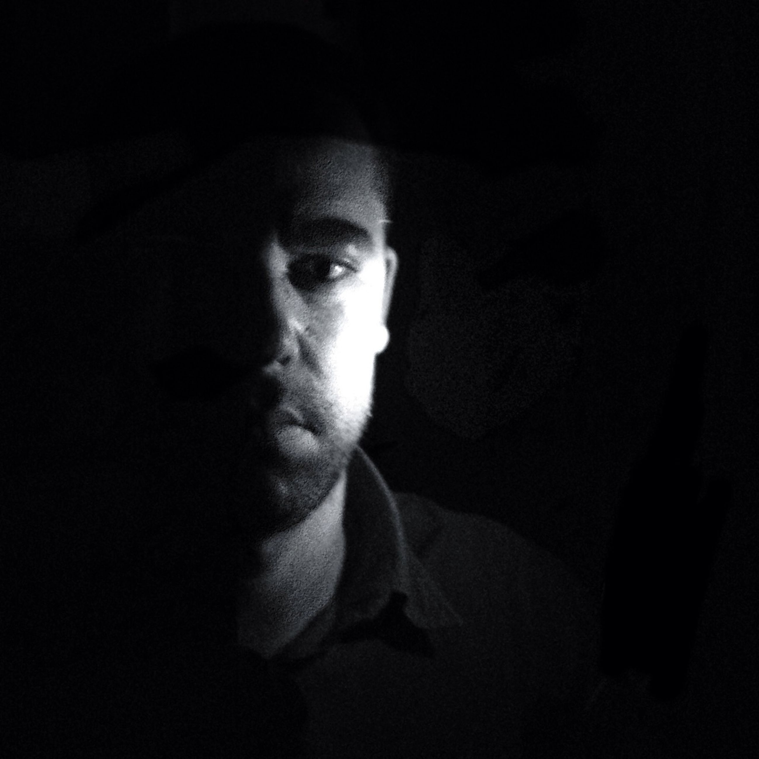 indoors, portrait, looking at camera, headshot, young adult, black background, lifestyles, front view, close-up, studio shot, dark, person, contemplation, young men, human face, leisure activity, serious