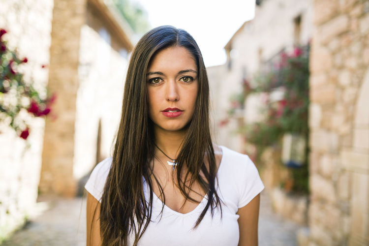 Beautiful young woman walking in a little old town. Beautiful Happy Lifestyle Old Town Woman Beautiful Woman Brunette Day Leisure Activity Lifestyles Looking At Camera One Person Outdoors People Portrait Real People Spring Time Springtime Summer Traveler Walking Young Adult Young Women