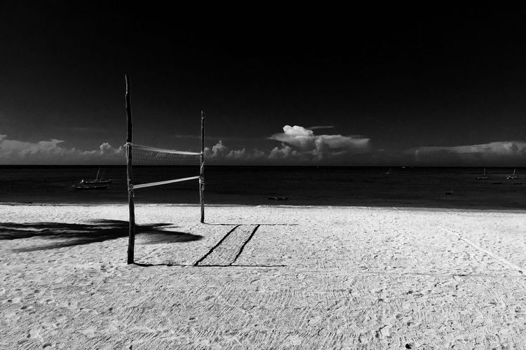 Volleyball net at beach against sky
