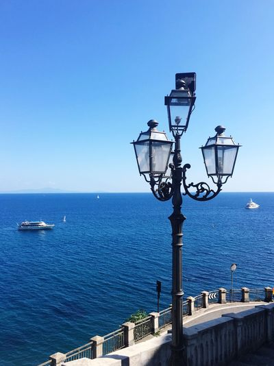 Street light by sea against clear blue sky