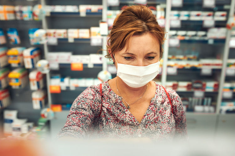 Woman shopping at pharmacy, buying medicines, wearing face mask to cover mouth and nose
