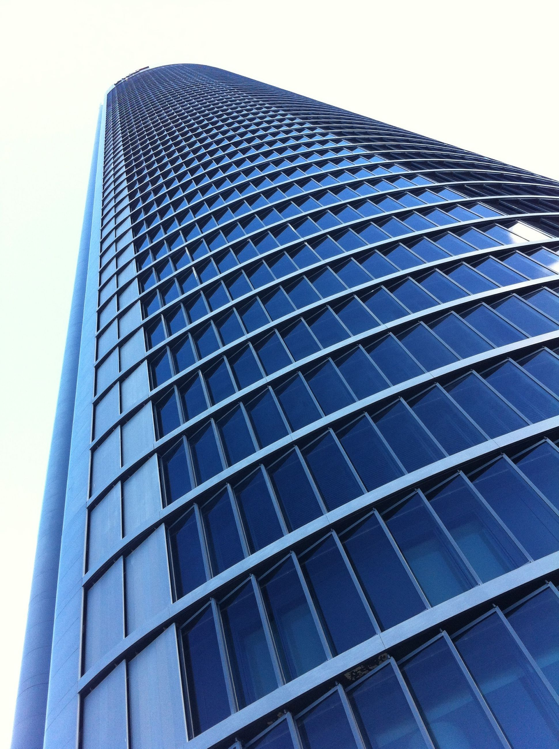 architecture, low angle view, building exterior, built structure, modern, office building, skyscraper, tall - high, city, glass - material, tower, building, reflection, clear sky, sky, day, tall, outdoors, no people, window