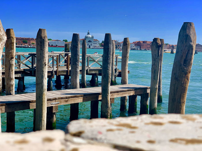 Wooden post on pier by sea against clear blue sky