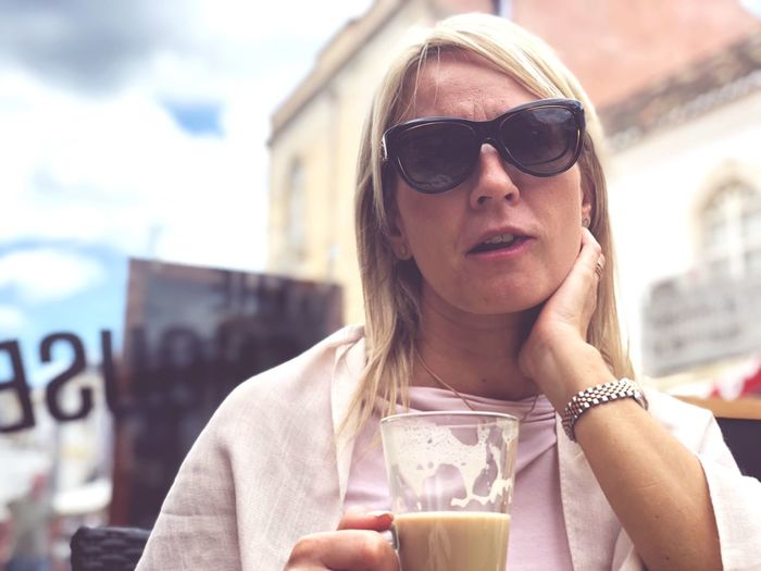 Portrait of woman wearing sunglasses while having coffee