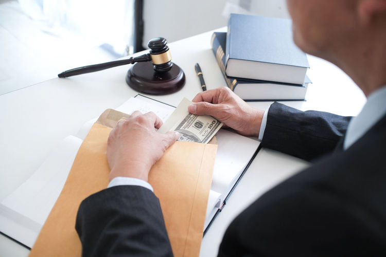 Midsection of judge putting money in envelope on table
