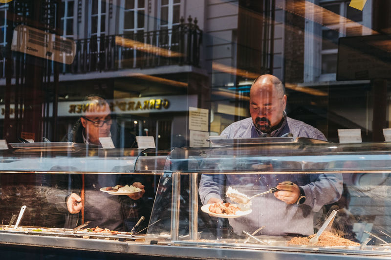 Real People London Uk Chinatown Soho Chinese Culture Area People Transparent Food And Drink Food Adult Males  Retail Display Store Mid Adult Men Restaurant Buffet Chinese Food All You Can Eat Looking Through Window Window Food And Drink Glass - Material Business Cafe