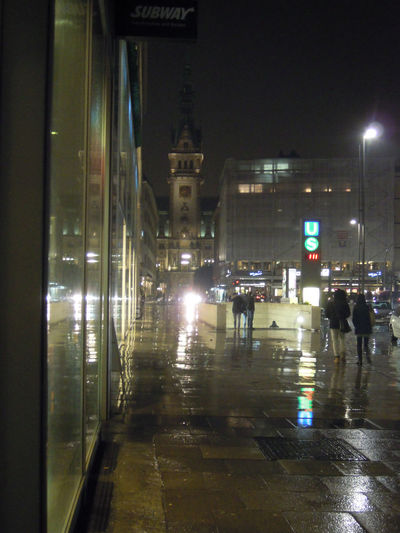 People walking on wet road in city at night