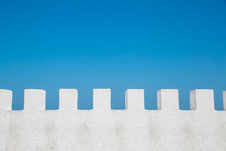 Low angle view of wall against clear blue sky