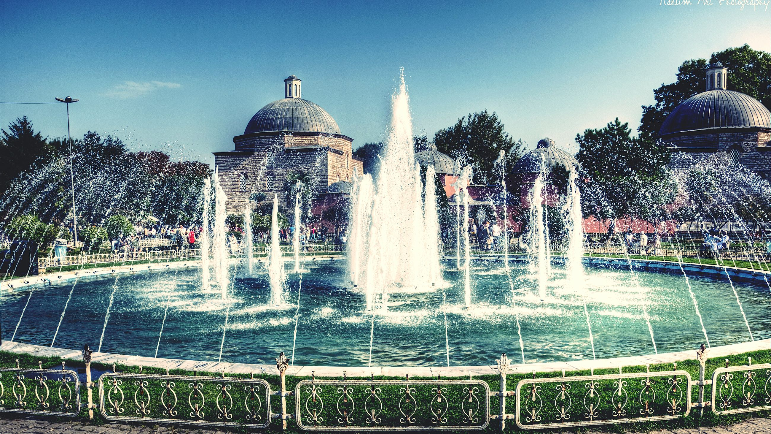 fountain, architecture, built structure, water, building exterior, famous place, spraying, travel destinations, motion, sculpture, tree, statue, splashing, tourism, international landmark, clear sky, travel, capital cities, art and craft, art